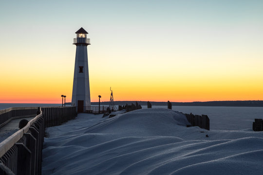 Winter Coastal Sunrise. Winter sunrise on the frozen shores of the Great Lakes with Wawatam Lighthouse in the St. Ignace harbor in Michigan's Upper Peninsula.