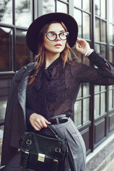 Outdoor waist up portrait of young beautiful girl, business woman posing in street, looking aside. Model wearing stylish clothes, trendy glasses, hat, holding bag, briefcase. Female fashion concept