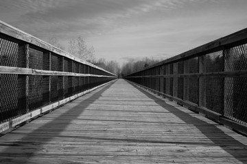 The Long Journey. Long wooden footbridge with a diminishing perspective in horizontal orientation in black and white. Wadhams to Avoca Rail Trail. Avoca, Michigan.