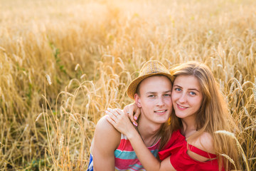 Happy young couple enjoying in the wheat field, summer season. Sunset light, flare light, copy space