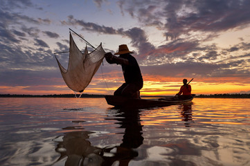 Silhouette fisherman trowing the nets on during sunset,during sunrise,Thailand