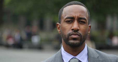 Black business man in city park face portrait serious