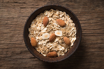 Dry rolled oat flakes oatmeal on old wooden