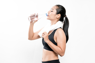 portrait of young woman wearing sport clothes and drinking water on white.