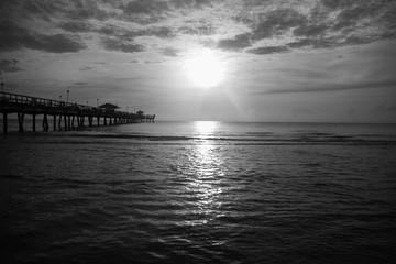 Sun over ocean with cloudy sky in black and white style