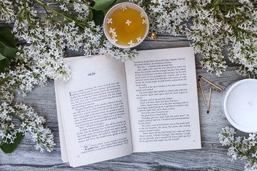 The book is in English surrounded by branches and flowers of white lilac, a mug of tea with lilac petals on a aged wooden vintage background and a white candle in a glass and matches.