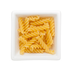 Uncooked Fusilli in a square bowl isolated on white background