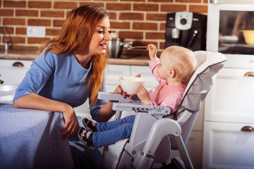 50f303cda Beautiful mother in blue dress feeding with spoon her cute baby girl ...