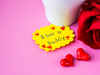 Father's day concept. I LOVE YOU DADY message with red rose, two red heart and gift on pink background