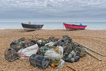 Pile of fishing gear in the foreground, two small fishing boats in the background on Bognor Regis beach.