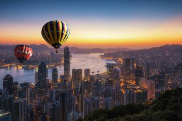 Hot air balloon over Victoria peak in morning, Hong Kong skyline