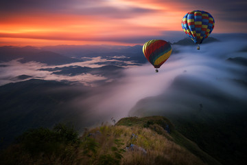 Hot air balloon over Pha Tang hill with beautiful mountain view and fog in morning, Chiang rai, Thailand