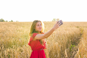technology, summer holidays, vacation and people concept - smiling young woman in red dress taking selfie by smartphone on cereal field