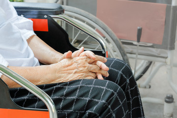 Elderly woman hand while waiting on wheelchair