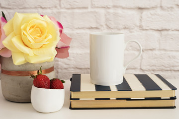 Coffee Cup Product Display. Coffee Mug On Striped Design Notebooks. Strawberries In Gold Bowl, Vase With Pink Roses