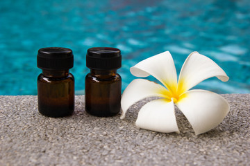 Bottles of aroma essential oil and flower of frangipani on the swimming pool background for spa theme.
