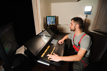 A lighting engineer works with lights technicians control on the concert show. Professional light mixer, mixing console. Equipment for concerts.