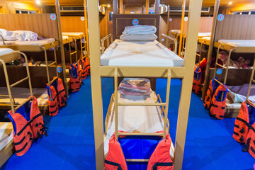 interior of a living cabin on a ship - with bunk beds and window.cabin with bunks for the crew on the old submarine.bunk beds on ferry boat to Koh Tao Island, Thailand