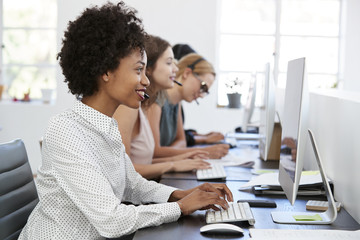 Young black woman working at computer in office with headset