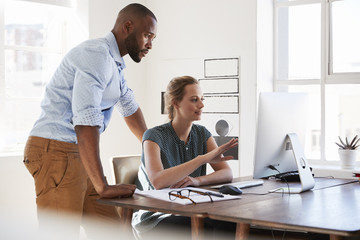 Man and woman talk in an office looking at computer screen