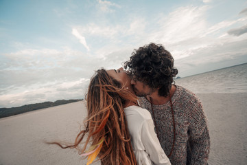 beautiful young couple kissing on beach at sunset