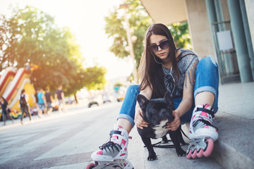 Warm summer colors and haze. Strong back light. Roller skates girl with sitting on city square with her French bulldog and enjoying hot afternoon.