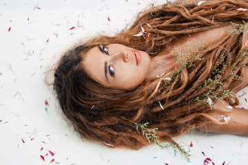 Beautiful adult girl with orchid petals on white background