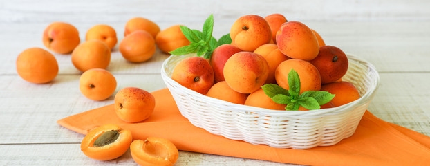 Ripe apricots in a basket on a light wooden background.