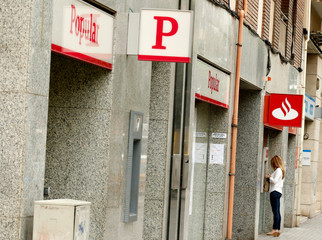 A woman uses a Santander's cash dispenser (ATM) next to a Banco Popular office in Barcelona
