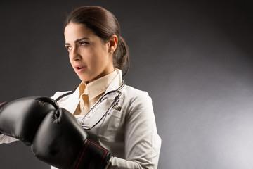 Medico donna con espressione decisa, in camice bianco, porta dei guantoni uniti che stanno ad indicare la lotta alle malattie  - sfondo bianco e nero