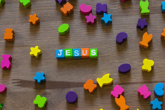 The word Jesus composed of children's wooden vivid alphabetic cubes in a mess from different parts of the game