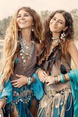 Two beautiful boho girls in ethnic jewelry outdoors