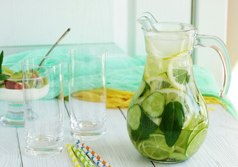 Detox water with cucumber, lemon, lime and mint in a jug on a white wooden background