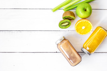 freshly squeezed juices for detox on wooden background top view