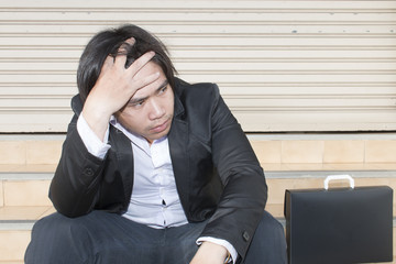 Sad young man in formalwear holding hand in hair