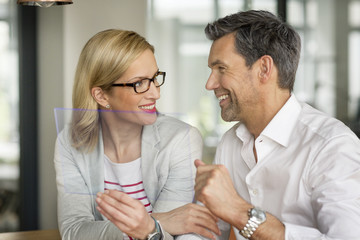 Smiling businessman and woman using futuristic portable device