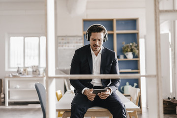 Businessman with tablet and headphones sitting on table