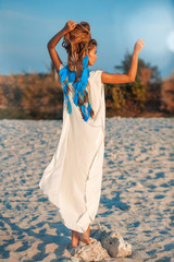 attractive bohemian style woman walking away on beach
