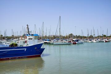 Boat and yacht on a bright sunny day in the seaport of Marina de las Dunas, Guardamar del Segura, Alicante, Spain.