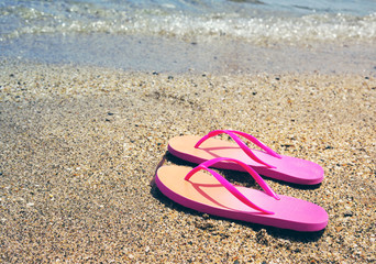 Pink flip flops on a beach against the sea in a summer sunny day, copy space. Vacation at the sea