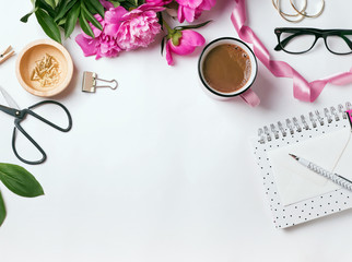 Stylish items and beautiful pink peonies. Woman's workplace concept