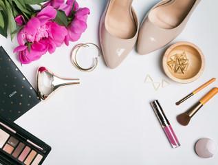 Stylish feminine accessories and pink peonies