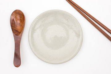 Traditional Japanese wooden chopstick with wooden spoon and white ceramic plate