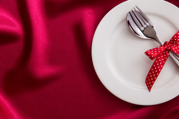 White empty plate with fork and spoon on red silk fabric for dinner setting