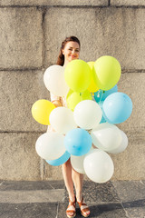 Young smiling woman with bunch of balloons standing against concrete wall at summer day