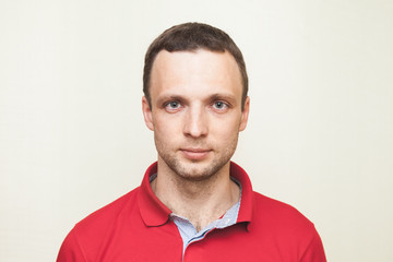 Young adult European man in red polo shirt