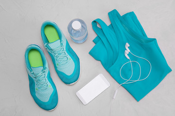 Flat light blue athletic shoes, a bottle of water, a T-shirt and headphones on a gray concrete background. The concept of a heal