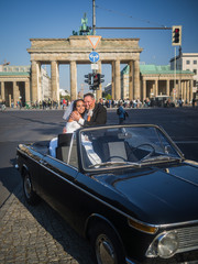 Newlywed couple sitting in an oldtimer at Brandenburger Gate