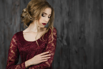 Beautiful elegant lady standing in a red long evening dress