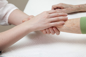 Hands of young beautician giving senior woman a manicure.